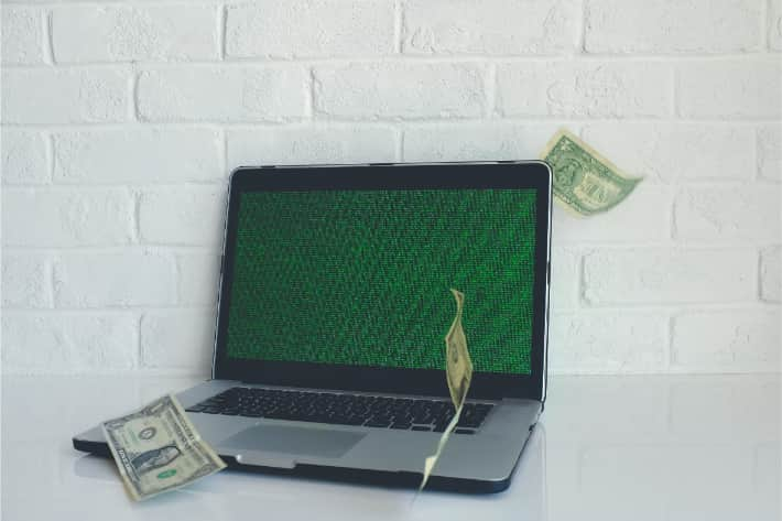 Hacked laptop with American dollar bills falling