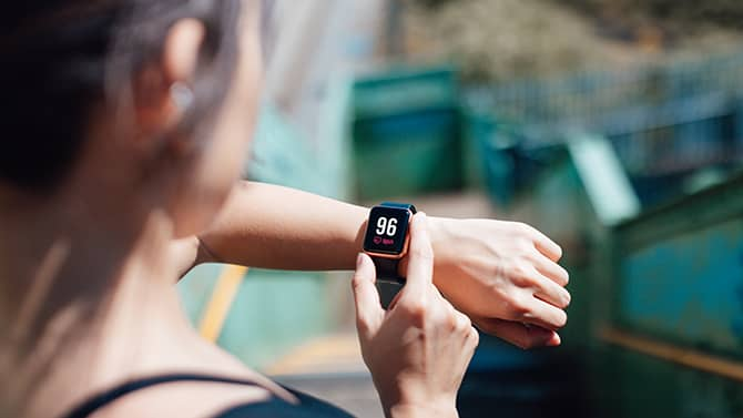 A woman uses a fitness app on her phone, synced to a wearable monitoring device on her wrist.