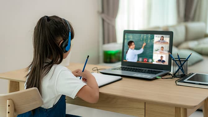 The Children's Online Privacy Protection Act is designed to protect children under 13 from having their personal information collected on the internet. Image shows a young girl using a laptop for remote learning.